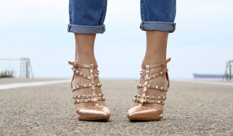 vue sur le bas des jambes d'une femme qui porte un jean et des chaussures à talons à clous