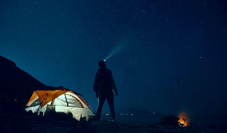 tente camping avec homme debout devant dans la nuit
